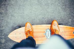 Mann mit Anzug auf dem Skateboard